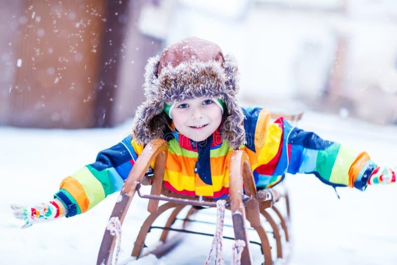 Leuk weinig grappige jongen in kleurrijke de winterkleren die pret hebben met royalty-vrije stock afbeeldingen