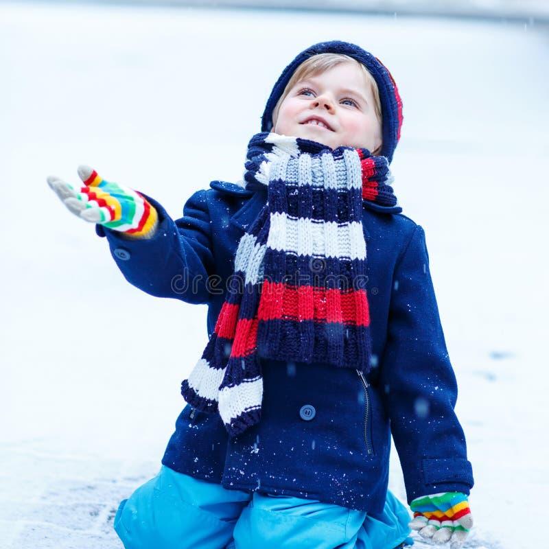 Leuk weinig grappige jongen in kleurrijke de winterkleren die pret hebben met stock afbeeldingen