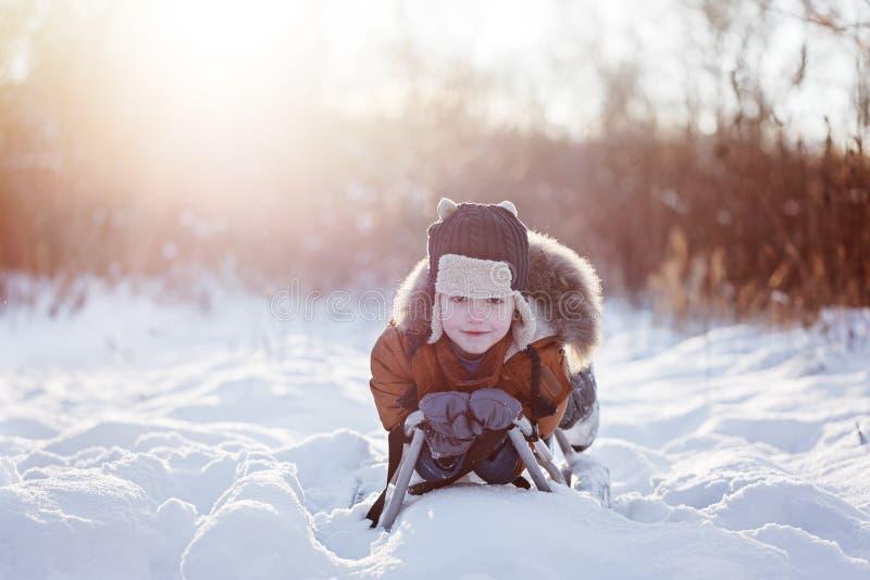 Leuk weinig grappige kindjongen in warme de winterkleren die pret op sneeuwslee hebben, in openlucht tijdens sneeuwval stock fotografie