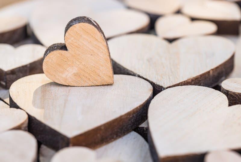 Leuk weinig hart op vele houten hartenachtergrond, liefdesymbool, close-up royalty-vrije stock fotografie