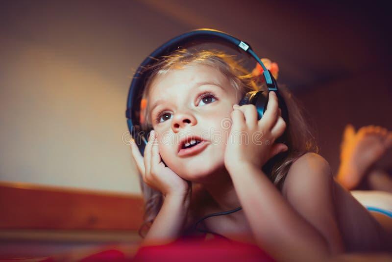 Leuk weinig jong geitje het luisteren muziek die op bed liggen royalty-vrije stock afbeeldingen