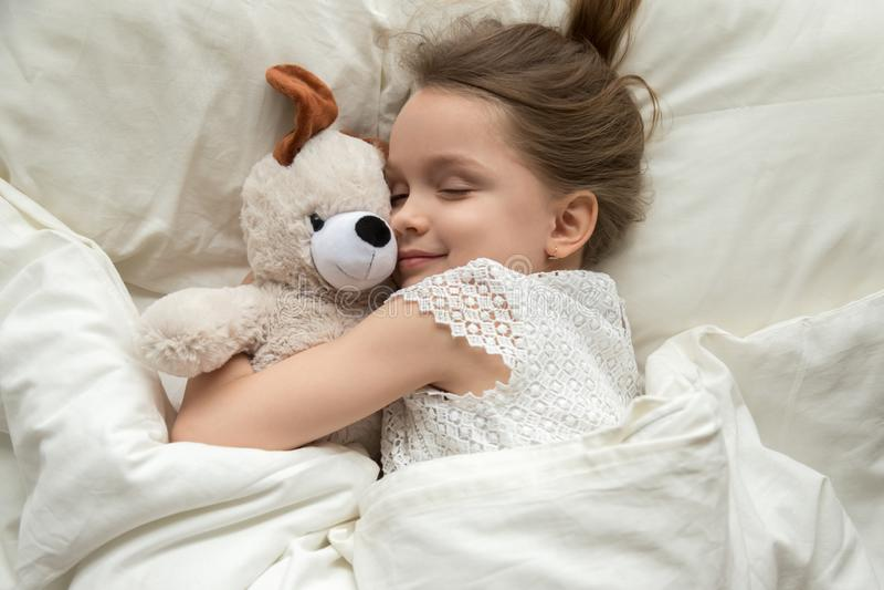 Leuk weinig jong geitjemeisje die teddybeerslaap in bed koesteren stock foto's