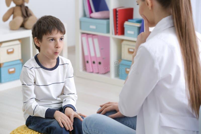 Leuk weinig jongen bij toespraaktherapeut stock foto's