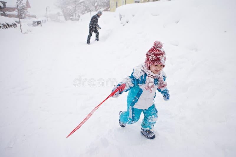 Leuk weinig jongen in blauw de winterkostuum, spelen openlucht in de sneeuw stock foto