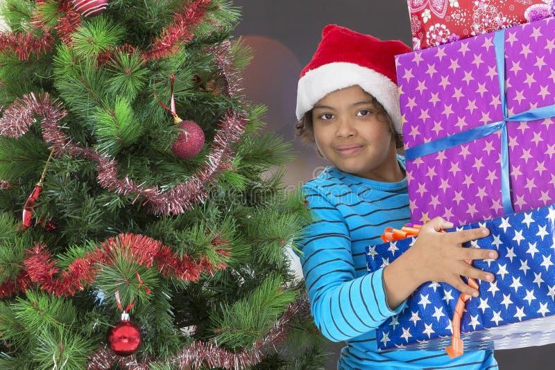 Leuk weinig jongen in de holdingsgift van de santahoed dichtbij Kerstboom stock fotografie