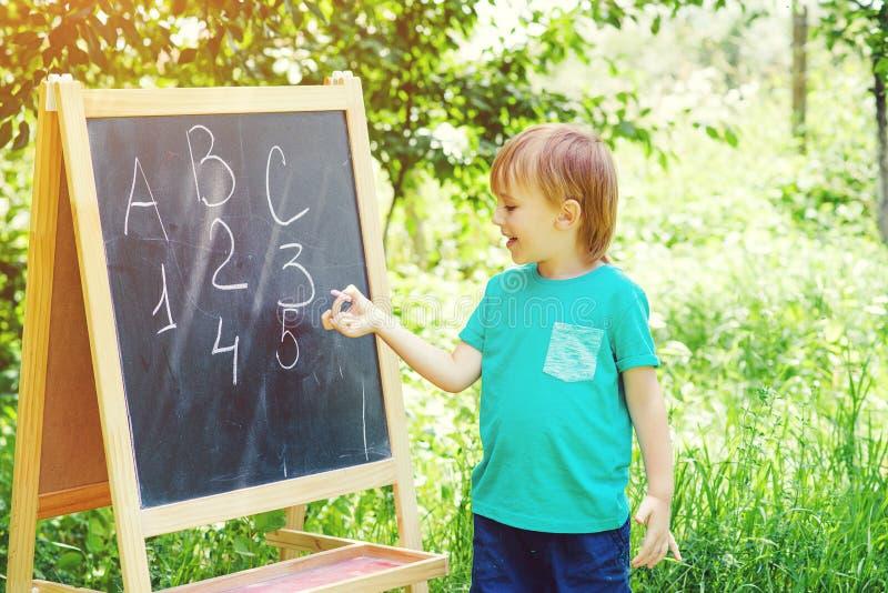 Leuk weinig jongen die bij bord schrijvend letters en getallen openlucht praktizeren Terug naar School royalty-vrije stock foto