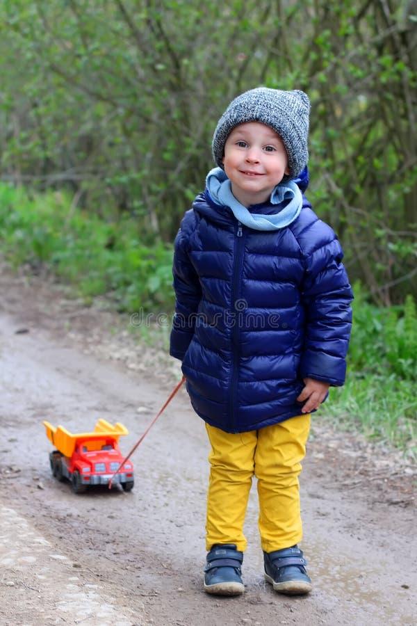 Leuk weinig jongen die in de lente buiten spelen Het kind van twee jaar draagt een vrachtwagen op een koord Glimlach, positieve e royalty-vrije stock foto's
