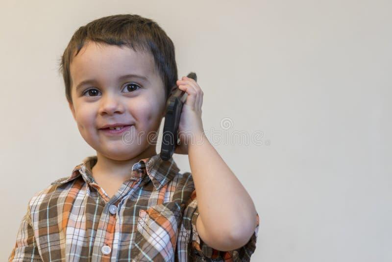 Leuk weinig jongen die door mobiele telefoon op lichte achtergrond spreken Gelukkig weinig jongen die en op smartphone zich thuis stock foto