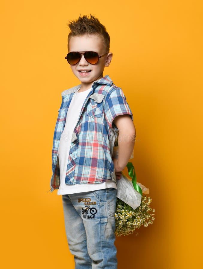 Leuk weinig jongen die een boeket van bloemen houden royalty-vrije stock foto's