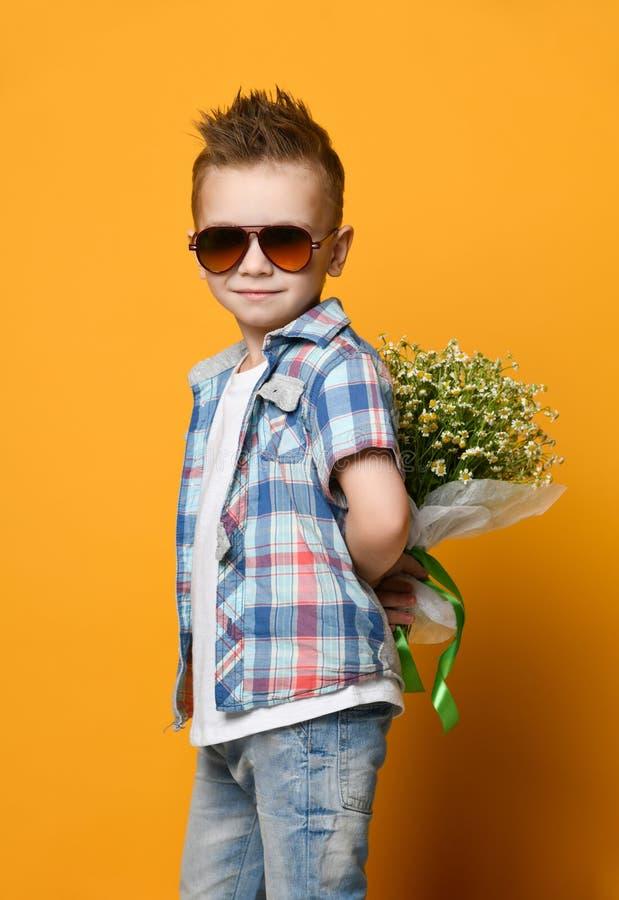 Leuk weinig jongen die een boeket van bloemen houden stock afbeelding