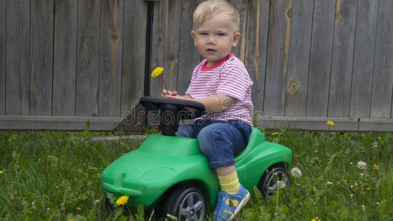 Leuk weinig jongen die een groene machine berijden royalty-vrije stock foto