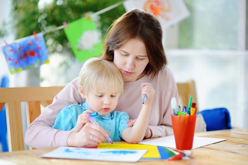 Leuk weinig jongen die en met kleurrijke tellerspennen bij kleuterschool trekken schilderen stock afbeelding