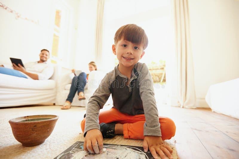 Leuk weinig jongen die en in woonkamer trekken kleuren royalty-vrije stock foto's