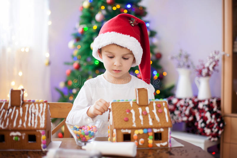 Leuk weinig jongen, die het huis van peperkoekkoekjes maken voor Kerstmis stock afbeelding