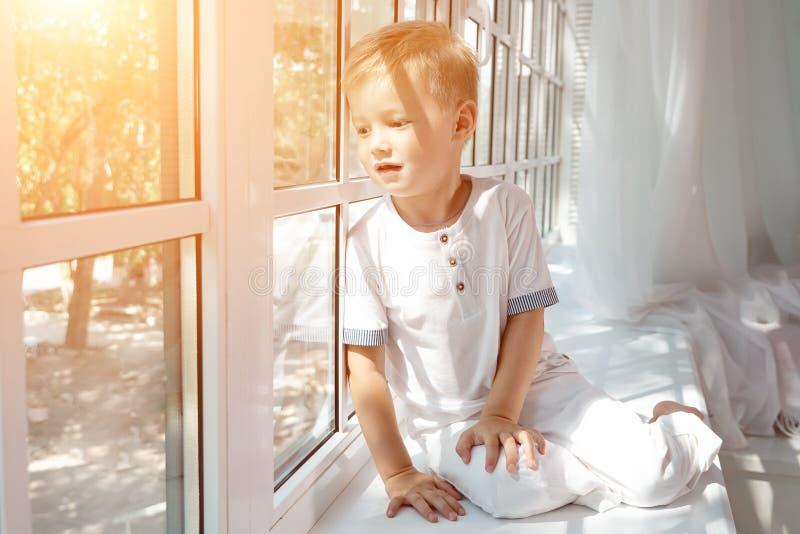 Leuk weinig jongen die in het venster kijken royalty-vrije stock foto's