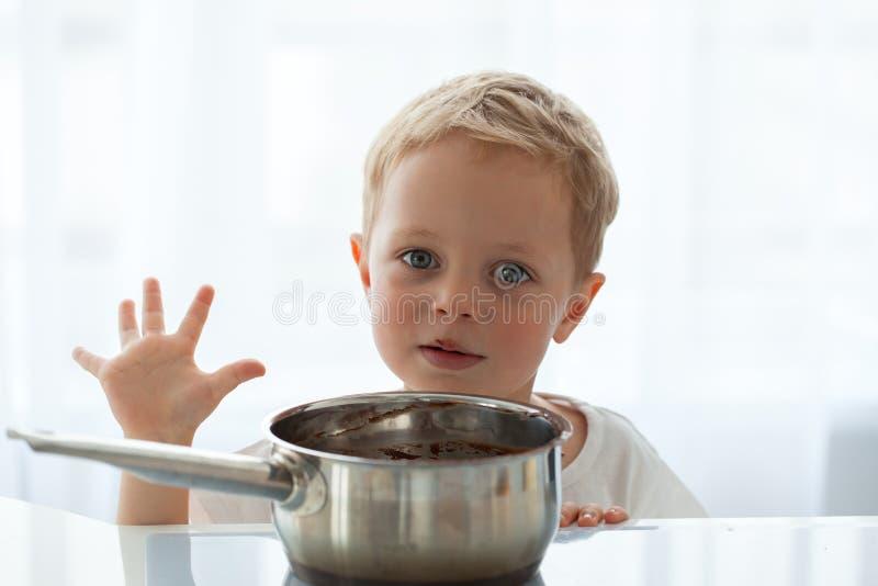 Leuk weinig jongen die Kerstmiskoekjes thuis voorbereiden stock afbeeldingen