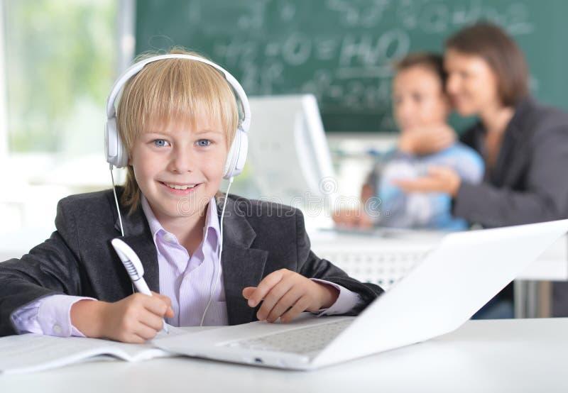 Leuk weinig jongen die laptop met behulp van stock fotografie