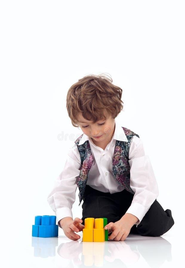 Leuk weinig jongen die met bouwreeks speelt stock fotografie