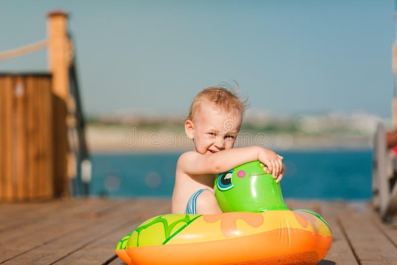 Leuk weinig jongen die met reddingsboei bij de kust spelen stock foto's