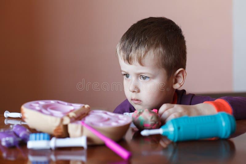 Leuk weinig jongen die met veelkleurige plasticine spelen Jongen het spelen met speelgoed Tandhulpmiddelen Grappig gezicht Het po stock afbeelding