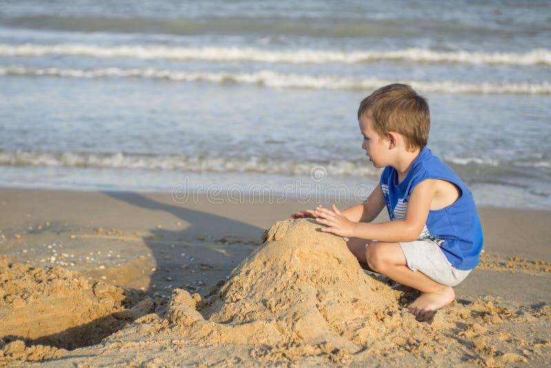 Leuk weinig jongen die met zand op tropisch strand spelen stock afbeeldingen