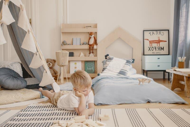 Leuk weinig jongen die op de vloer van zijn modieuze Skandinavische slaapkamer, echte foto leggen stock foto