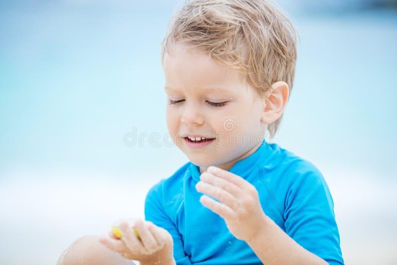 Leuk weinig jongen die op het strand spelen: vullende vormvorm met zand royalty-vrije stock foto's