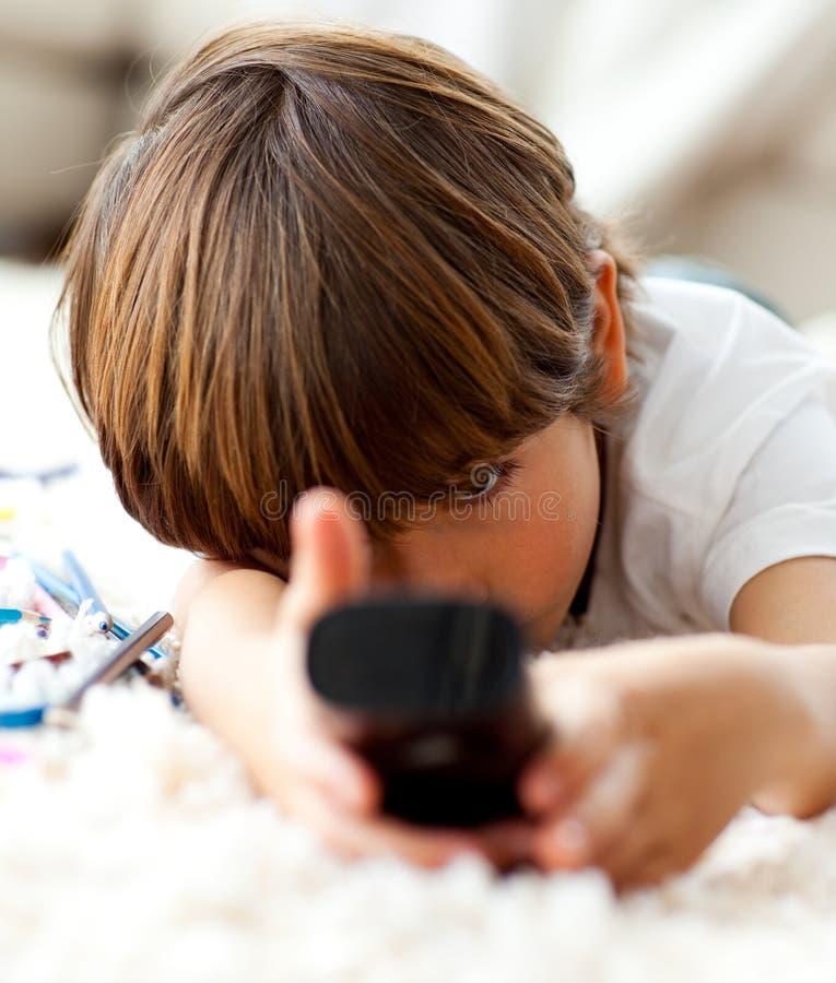 Leuk weinig jongen die op TV let liggend op de vloer stock foto