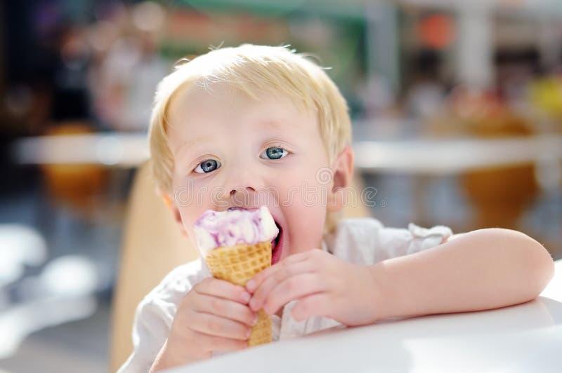 Leuk weinig jongen die Roomijsgelato in binnen koffie eten stock fotografie