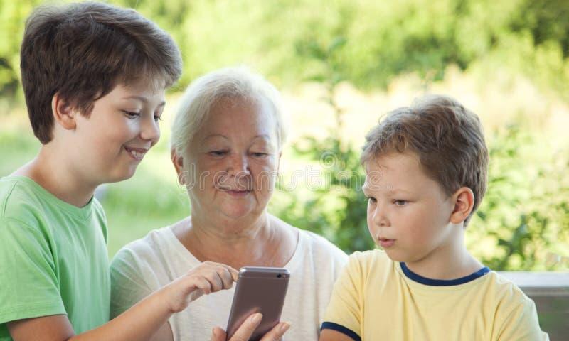 Leuk weinig jongen die smartphone met oma thuis veranda gebruiken royalty-vrije stock afbeeldingen