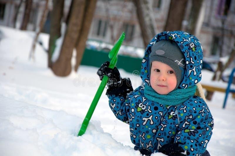 Leuk weinig jongen die sneeuw scheppen royalty-vrije stock afbeeldingen