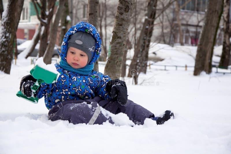 Leuk weinig jongen die sneeuw scheppen royalty-vrije stock foto's