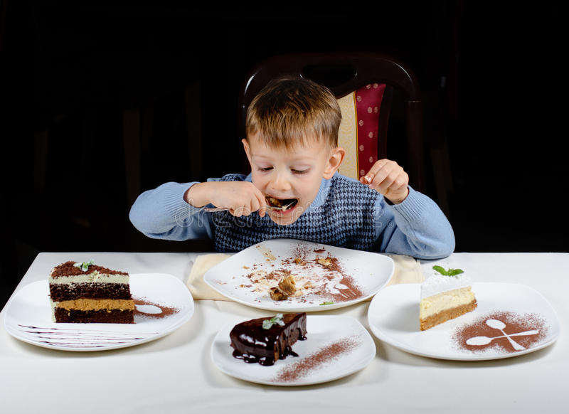 Leuk weinig jongen die van een traktatie van partijcakes genieten royalty-vrije stock foto