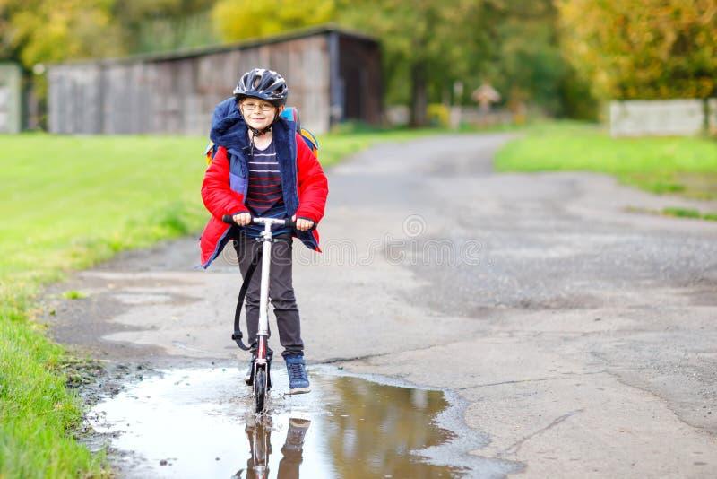 Leuk weinig jongen die van het schooljonge geitje op duwautoped op de manier aan of van school berijden Schooljongen van 7 jaar d stock fotografie