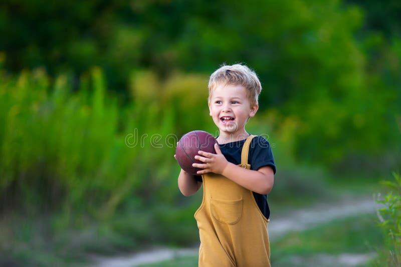 Leuk weinig jongen die in vrijetijdskleding met bal spelen stock foto's