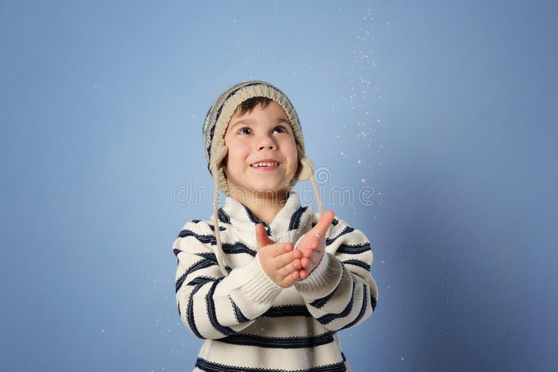 Leuk weinig jongen die in warme kleren met sneeuw spelen royalty-vrije stock fotografie