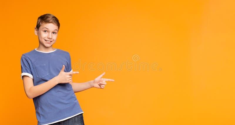 Leuk weinig jongen die weg op oranje achtergrond richten royalty-vrije stock afbeeldingen