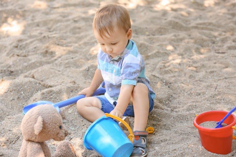 Leuk weinig jongen die in zandbak in openlucht spelen stock afbeeldingen