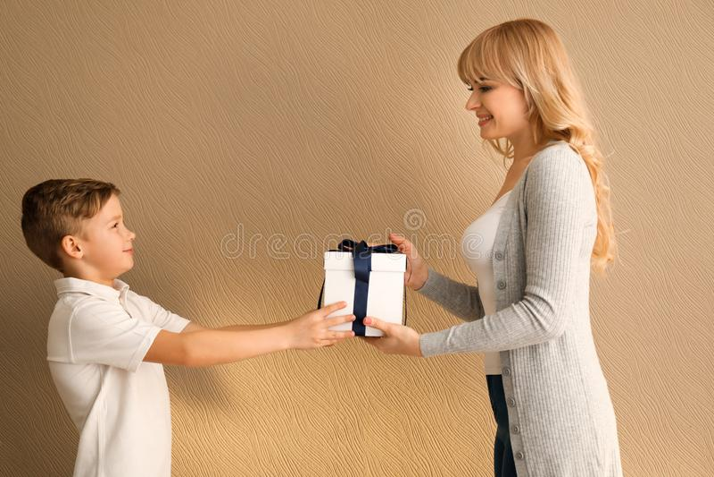 Leuk weinig jongen die zijn doos van de moedergift op kleurenachtergrond geven royalty-vrije stock foto's