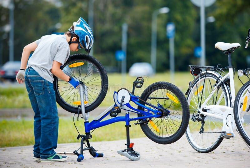 Leuk weinig jongen die zijn fiets in openlucht herstellen stock foto