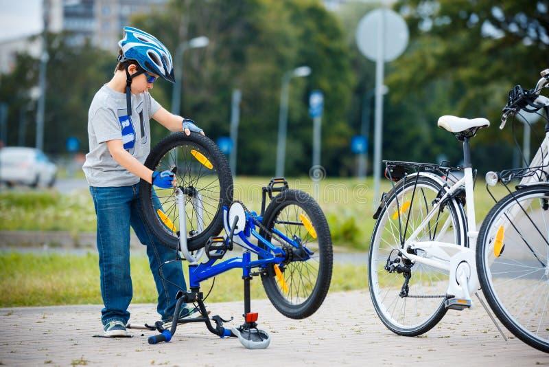 Leuk weinig jongen die zijn fiets in openlucht herstellen stock fotografie