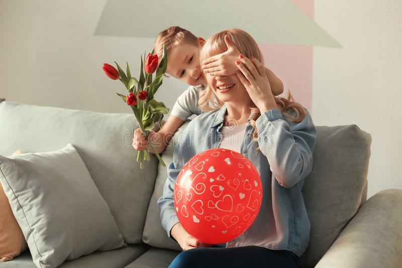 Leuk weinig jongen die zijn moeder met tulpenboeket thuis verrassen stock afbeelding