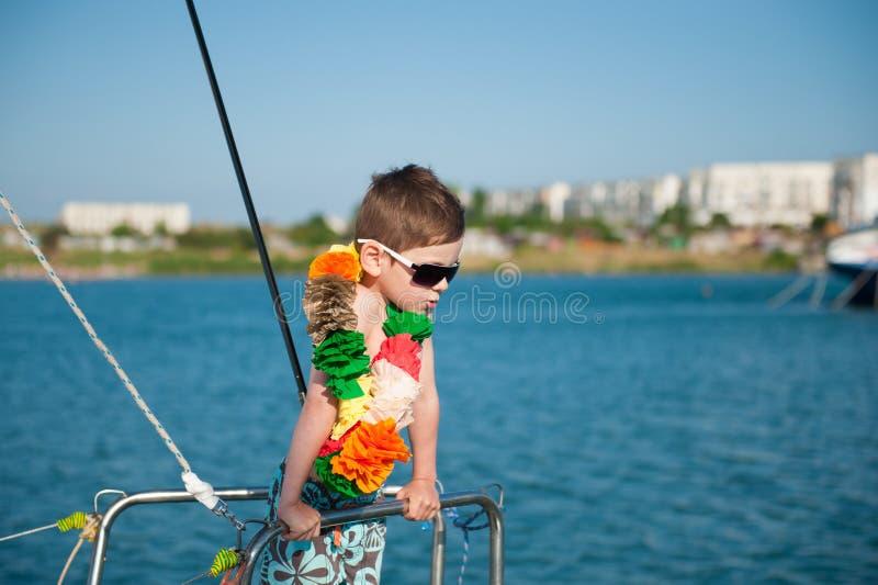 Leuk weinig jongen die zonnebril en Hawaiiaanse decoratie aan boord dragen royalty-vrije stock afbeelding
