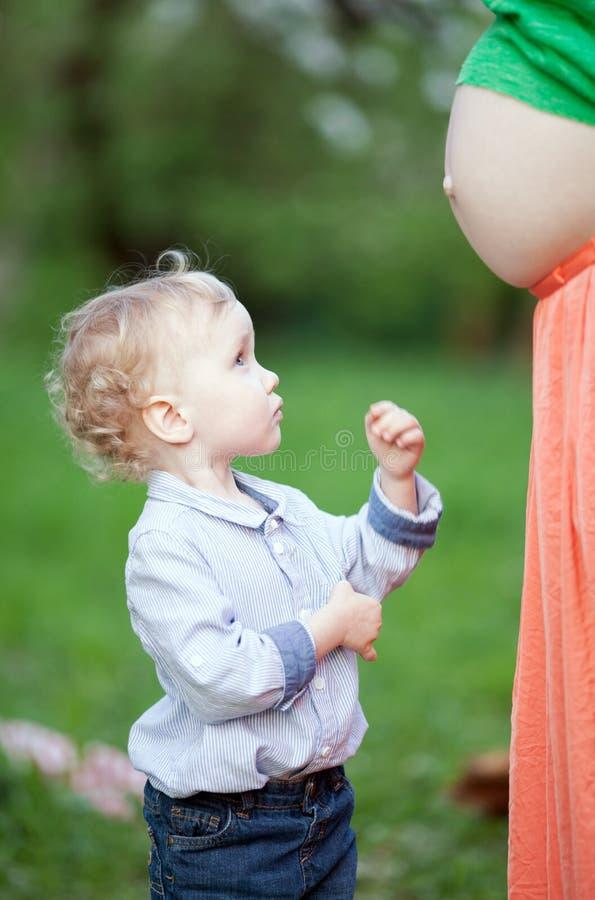 Leuk weinig jongen die zwangere mamma'sbuik bekijken royalty-vrije stock afbeeldingen