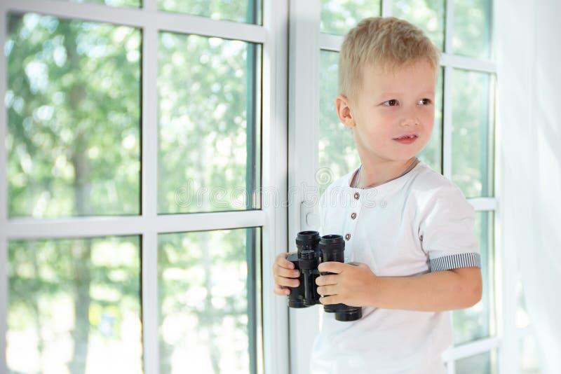 Leuk weinig jongen die zwarte binoculair houden en vanaf de camera kijken stock foto