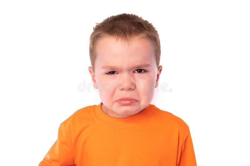 Leuk weinig jongen in een heldere t-shirt met scheur-bevlekt die gezicht, op witte achtergrond wordt geïsoleerd royalty-vrije stock fotografie