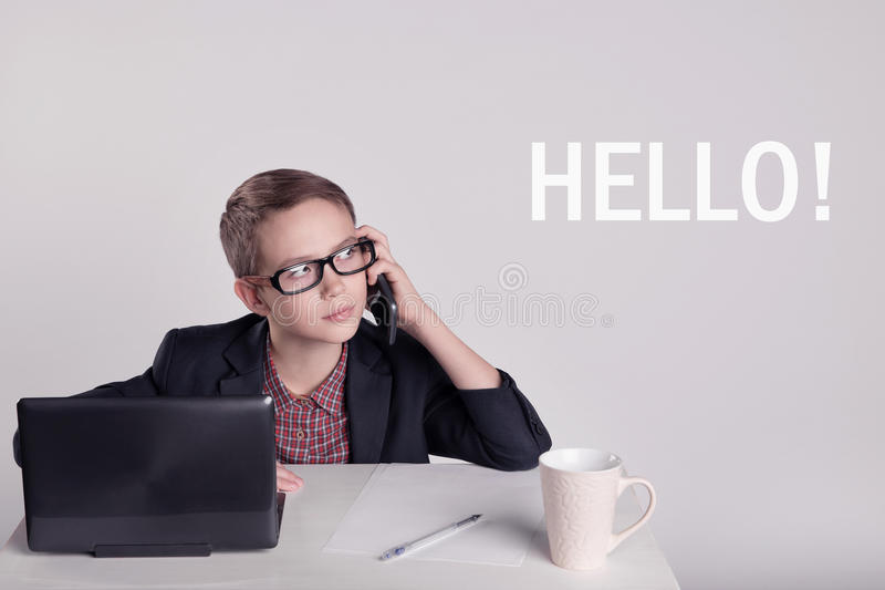 Leuk weinig jongen in een kostuum die op de telefoon spreken stock afbeeldingen