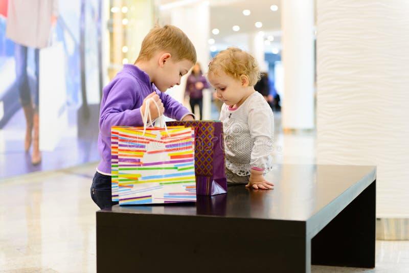Leuk weinig jongen en meisjes het inspecteren het winkelen zakken in wandelgalerij stock afbeeldingen