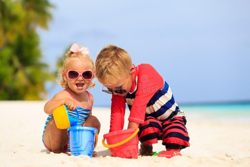 Leuk weinig jongen en peutermeisjesspel met zand op strand stock afbeeldingen