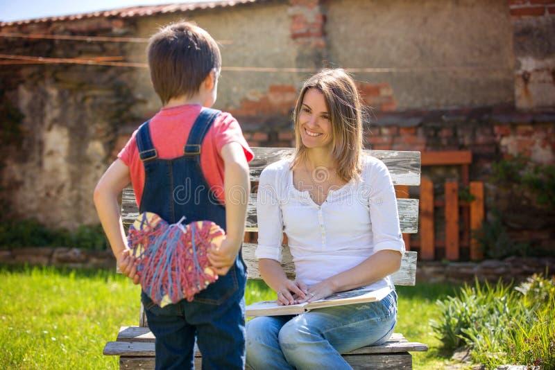 Leuk weinig jongen, geven huidig aan zijn mamma voor Moedersdag in Th royalty-vrije stock afbeeldingen